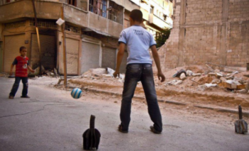 two_children_playing_football_using_old_mortars_as_goal