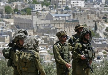 Israeli troops stand guard as Palestinia
